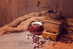 Coffee cup and old vintage coffee grinder. Focus on coffee cup Royalty Free Stock Photography
