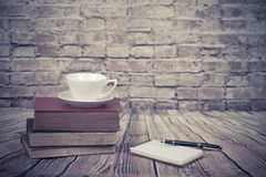 Coffee Cup On Old Book Set Up On Wood Table And Brick Wall Stock Photography