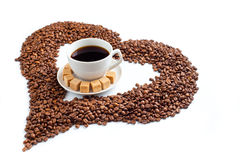 Coffee Cup On Pile Of Beans In Form Of Heart