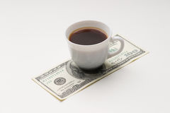 Coffee cup and one hundred U.S. dollars Stock Image