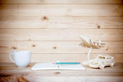 Coffee cup and open book with pen on wooden table. royalty free stock images