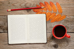 Coffee cup, open diary, pencil and autumn leaves Stock Photography