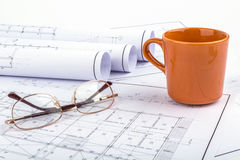Coffee cup orange, calculator, and  Spectacles on the plan drawi Royalty Free Stock Photography