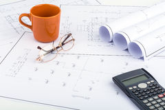 Coffee cup orange, calculator, and  Spectacles on the plan drawi Stock Images