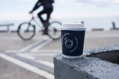 A coffee cup with a bicyclist in background stock image