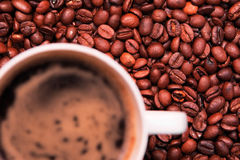 Coffee cup over coffee beans Royalty Free Stock Image