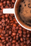 Coffee cup over coffee beans Stock Images