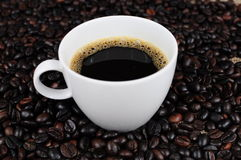 Coffee cup over coffee beans. Coffee cup over scattered coffee beans Stock Images