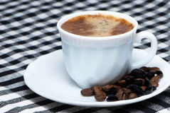 Coffee cup over dark roasted coffee beans Royalty Free Stock Image