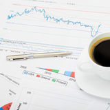 Coffee cup over different financial charts - close up studio shot Stock Photos
