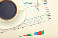 Coffee cup over financial charts. Filtered image: cross processed vintage effect. Royalty Free Stock Photography
