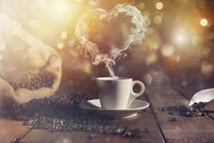 Coffee cup with a smoke shaped as an hearth. Coffee cup over a wooden table with a smoke shaped as an hearth stock images