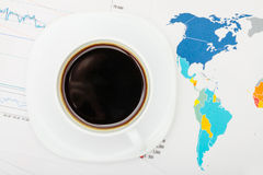 Coffee cup over world map and financial documents - view from top. Studio shot royalty free stock images