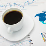 Coffee cup over world map and financial market charts - close up shot Stock Photo