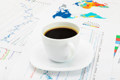 Coffee cup over world map and some financial documentation - close up studio shot Royalty Free Stock Photos