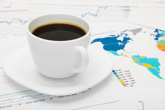 Coffee cup over world map and some financial documents - business concept Royalty Free Stock Images