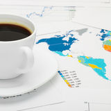Coffee cup over world map and some financial documents - close up Stock Photos