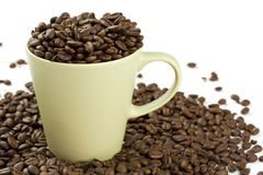 Coffee Cup Overflow. A coffee cup overflowing with whole coffee beans Royalty Free Stock Photos