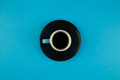 Coffee cup overhead on bright blue background. Minimalist shot of coffee cup on bright background Royalty Free Stock Photo
