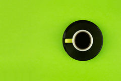 Coffee cup overhead on bright green background. Minimalist shot of coffee cup on bright background Stock Photography
