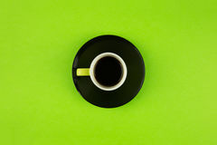 Coffee cup overhead on bright green background. Minimalist shot of coffee cup on bright background Royalty Free Stock Photo