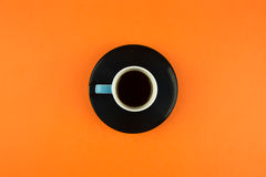 Coffee cup overhead on bright orange background. Minimalist shot of coffee cup on bright background Royalty Free Stock Photo
