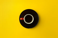 Coffee cup overhead on bright yellow background. Minimalist shot of coffee cup on bright background Royalty Free Stock Photography
