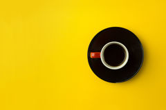 Coffee cup overhead on bright yellow background. Minimalist shot of coffee cup on bright background Royalty Free Stock Photos