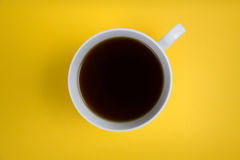 Coffee cup overhead on bright yellow background. Mininalist shot of coffee cup royalty free stock photo
