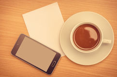 Coffee cup with paper note and smart phone on table Royalty Free Stock Photo