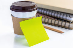 Coffee cup and paper note on white table. Stock Image