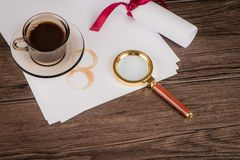 Coffee cup, paper sheets and detective hat. On old Wooden table stock photos
