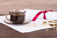 Coffee cup, paper sheets and detective hat. On old Wooden table royalty free stock photo