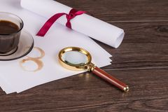 Coffee cup, paper sheets and detective magnifying glass. On old Wooden table stock images