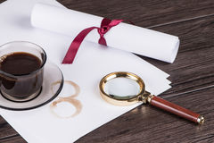 Coffee cup, paper sheets and detective magnifying glass. On old Wooden table royalty free stock photography