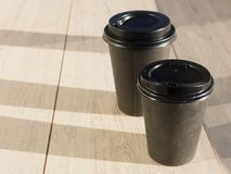 Coffee cup paper with wooden background, the glasses in the sunlight Stock Images