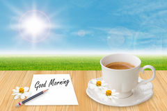 Coffee cup and paper with word Good morning. On table in morning Royalty Free Stock Photo