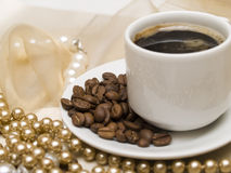 Coffee cup and pearl beads Stock Photos