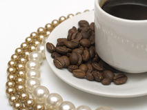 Coffee cup and pearl beads Stock Images