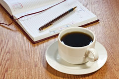 Coffee cup, pen, opened organizer Stock Image
