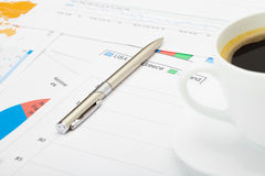 Coffee cup and pen over financial charts Stock Photo