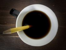 Coffee cup with pencil. Closeup of a cup of black coffee with yellow pencil Royalty Free Stock Photo