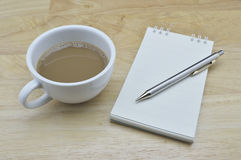 Coffee cup with pencil and notebook on table Stock Image