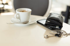 Coffee cup with phone and leather wallet Stock Images