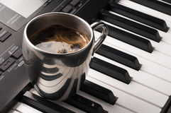 Coffee cup on piano keyboard Stock Photography