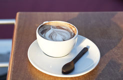 The coffee cup with a picture and a chocolate spoon Royalty Free Stock Images