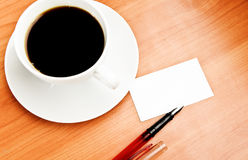 Coffee cup, piece of paper and pen on the wooden table Stock Photo