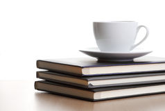 Coffee cup on a pile of notebooks Royalty Free Stock Image
