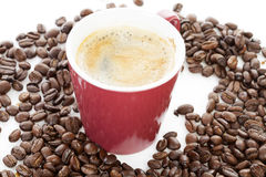 Coffee cup in pile of roasted beans Stock Photos