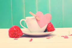 Coffee cup with pink heart tag and carnations Royalty Free Stock Image